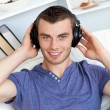 Relaxed young man listening to music looking at the camera — Stock Photo