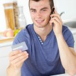 Attractive young man talking on phone holding a card looking at — Stockfoto