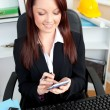 Smiling young businesswoman using her calculator — Stock Photo