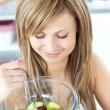 Pretty young woman eating a fruit salad in the kitchen — Stock Photo