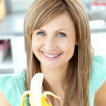 Smiling young holding a banana looking at the camera — Stock Photo