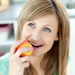 Captivating caucasian woman eating an apple in the kitchen — Stock Photo #10830727