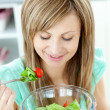 Cute young woman eating a healthy salad in the kitchen — ストック写真