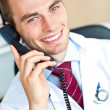 Portrait of an attractive doctor talking on phone smiling at the — Stock Photo #10830826