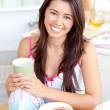 Beautiful asian woman having breakfast smiling at the camera — Stock Photo