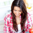 Merry female asian student doing math in the kitchen - Stock Photo