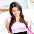 Cheerful asian woman using her laptop after shopping on the sofa — Stock Photo #10830877