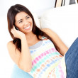 Delighted asian woman talking on phone sitting on the couch — Stock Photo