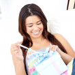 Royalty-Free Stock Photo: Excited young asian woman open a present sitting on the couch