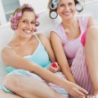 Stock Photo: Cheerful female friends doing pedicure and wearing hair rollers