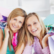 Glowing two women holding shopping bags smiling at the camera — Stock Photo
