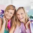 Delighted two women holding shopping bags smiling at the camera — Stock Photo #10831061