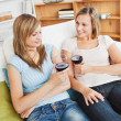 Charming two women drinking wine sitting on a sofa — Stock Photo #10831078
