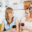 Happy two women drinking wine sitting on a sofa — Stock Photo #10831081