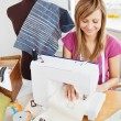 Bright woman sewing at home - Stock Photo