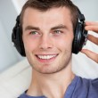 Handsome young man listening to music with headphones — Stock Photo