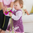 Adorable little girl holding flowers in the living-room — Stock Photo