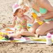 Stock Photo: Attentive mother at beach with her daughter