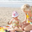 Stock Photo: Little girl using suncream at beach