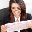 Smiling asian businesswoman reading a newspaper — Stock Photo