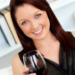 Elegant young woman holding a glass of wine at home — Stock Photo
