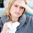 Stock Photo: Caucasiwomwith headache and tissues at home