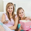 Relaxed female friends eating popcorn watching tv - Stock Photo