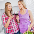 Smiling female friends drinking wine in the kitchen — Stock Photo