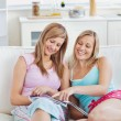 Pretty friends reading a magazine at home — Stock Photo