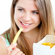 Radiant young woman eating fries — Stock Photo
