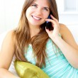 Glowing woman talking on phone at home — Stock Photo