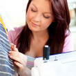 Serious young caucasian woman sewing in the kitchen - Stock Photo
