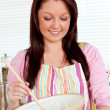 Confident woman cooking a cake at home — Stock Photo #10831694