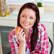 Radiant caucasian woman holding an apple sitting in the kitchen — Stock Photo