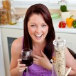 Cheerful woman eating her meal holding a glass of wine at home — Stock Photo