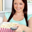 Charming caucasian woman holding a remote and popcorn in the liv — Stock Photo