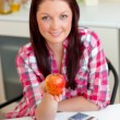 Serious caucasian woman holding an apple sitting in the kitchen — Stock Photo