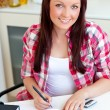Stock Photo: Radiant student doing her homework at home
