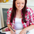 Cute student doing her homework at home - Stock Photo