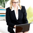 Stock Photo: Ambitious businesswomusing her laptop sitting on sofa