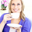 Bright woman enjoying her coffee sitting on the sofa — Stock Photo
