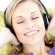 Delighted woman listening to music in the living-room — Stock Photo