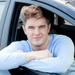 Stock Photo: Positive young man sitting in his car