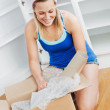 Stock Photo: Charming womunpacking box on floor