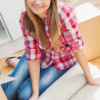 Stock Photo: Smiling womunpacking box on floor