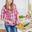 Joyful woman cutting pepper and cucumber at home — Stock Photo