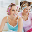 Female friends with hair rollers watching televison on the sofa - Stock Photo
