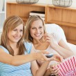 Two bright female friends watching televison on the sofa eating — Stock Photo