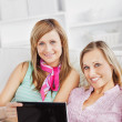 Two cheerful women using a laptop on the sofa — Stock Photo