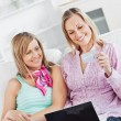 Two cheerful women using a laptop and holding a card on the sofa — Stock Photo